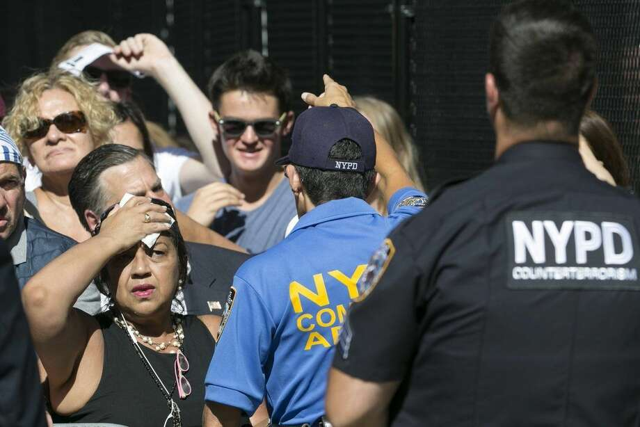People speak to members of the New York Police Department while waiting hours prior to the arrival of Pope Francis, Thursday, Sept 24, 2015, in New York. (Aristide Economopoulos /The Star-Ledger via AP, Pool)