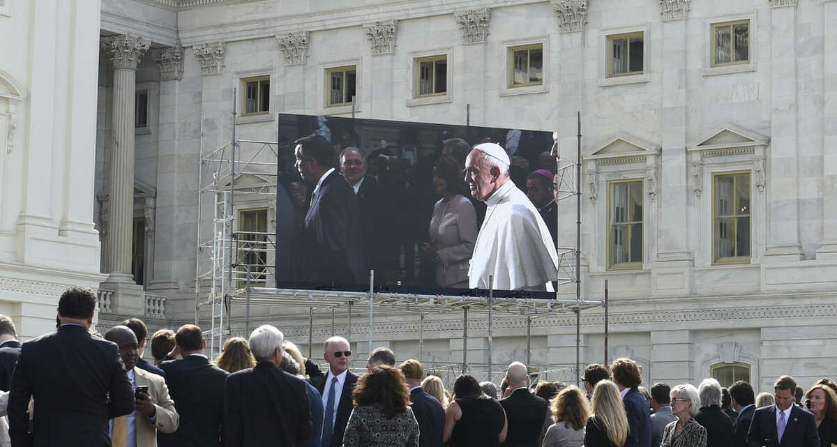 People watch Pope Francis on a large screen television from the West Front of the Capitol in Washington, Thursday, Sept. 24, 2015, as the Pope walks through Capitol Hill after he addressed a joint meeting of Congress . (AP Photo/Susan Walsh)