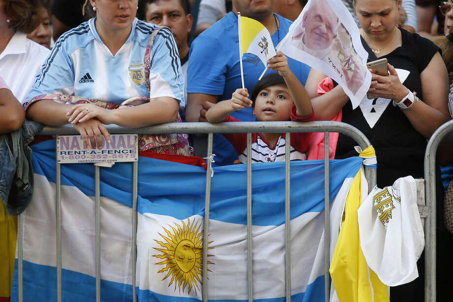 """A young supporter waves a Vatican flag behind a barricade on the perimeter of St. Patrick's Cathedral before the arrival of Pope Francis, Thursday, Sept. 24, 2015, in New York. Security screening will be just part of """"layers and layers and layers of protection"""" the pope will receive during his New York visit, visit, including a deployment of 6,000 extra police officers and specialized counterterrorism units, said John Miller, the NYPD's top security official. (AP Photo/John Minchillo)"""