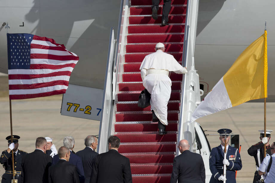 Pope Francis carries his own briefcase up the stairs before boarding his plane before leaving from Andrews Air Force Base, Md., en route to New York, Thursday, Sept. 24, 2015. (AP Photo/Jacquelyn Martin)