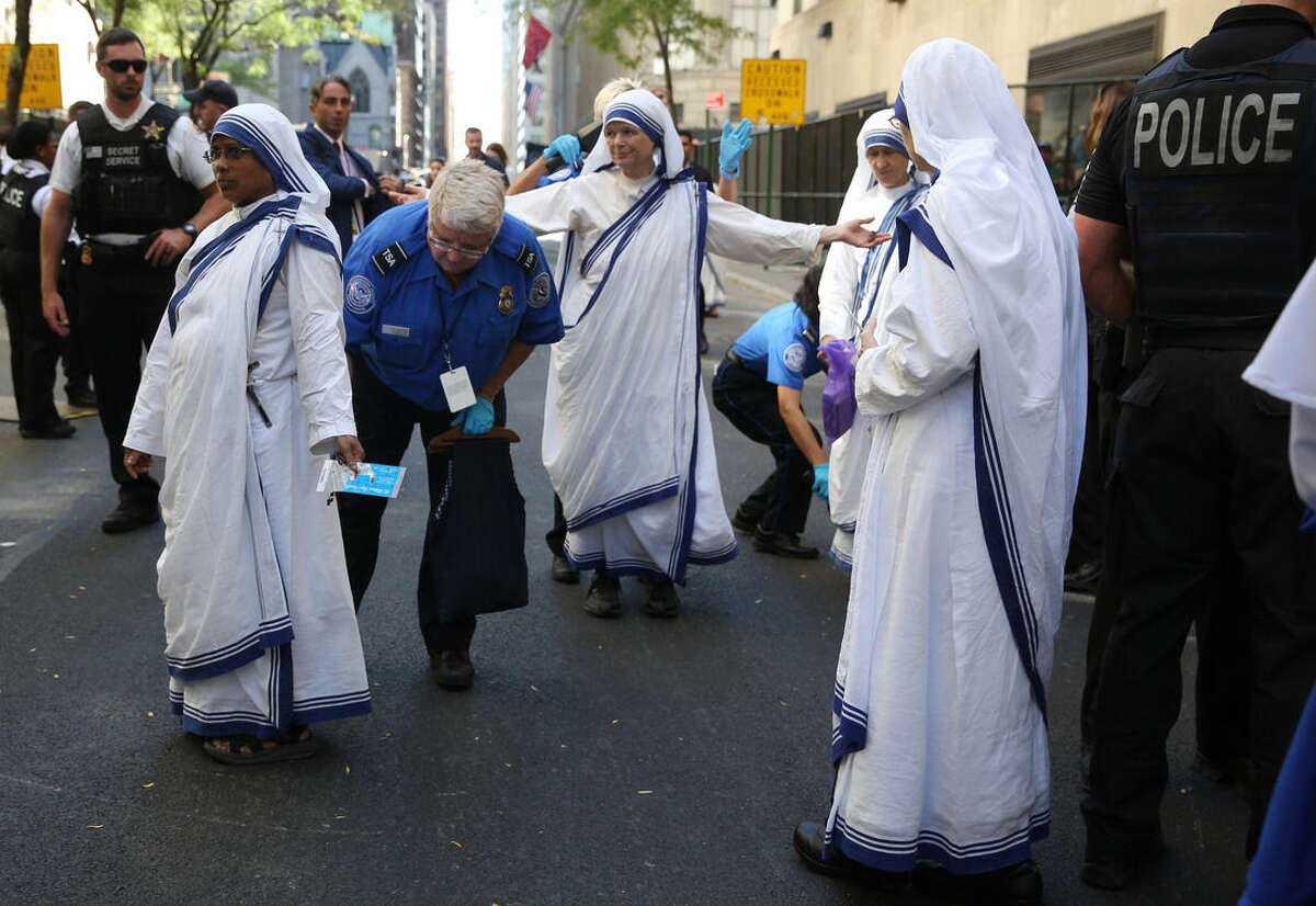 A New York City police officer searches nuns outside St. Patrick's Cathedral prior to the arrival of Pope Francis in New York, Thursday Sept. 24, 2015. (Damon Winter/The New York Times via AP, Pool)