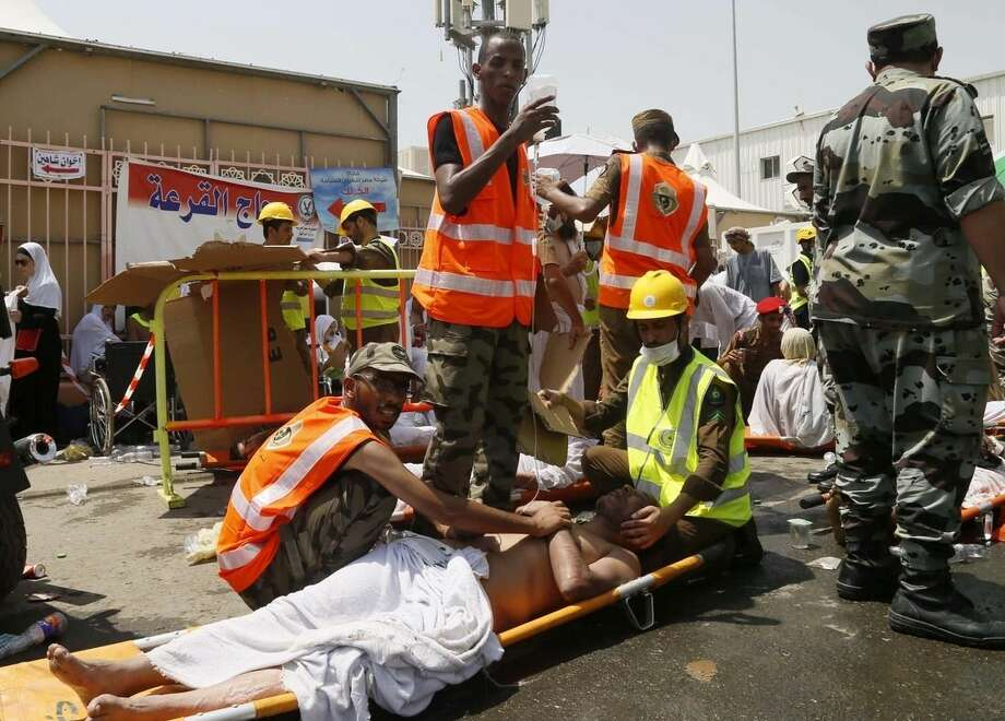 Rescue workers attend to victims of a stampede in Mina, Saudi Arabia during the annual hajj pilgrimage on Thursday, Sept. 24, 2015. Hundreds were killed and injured, Saudi authorities said. The crush happened in Mina, a large valley about five kilometers (three miles) from the holy city of Mecca that has been the site of hajj stampedes in years past. (AP Photo)