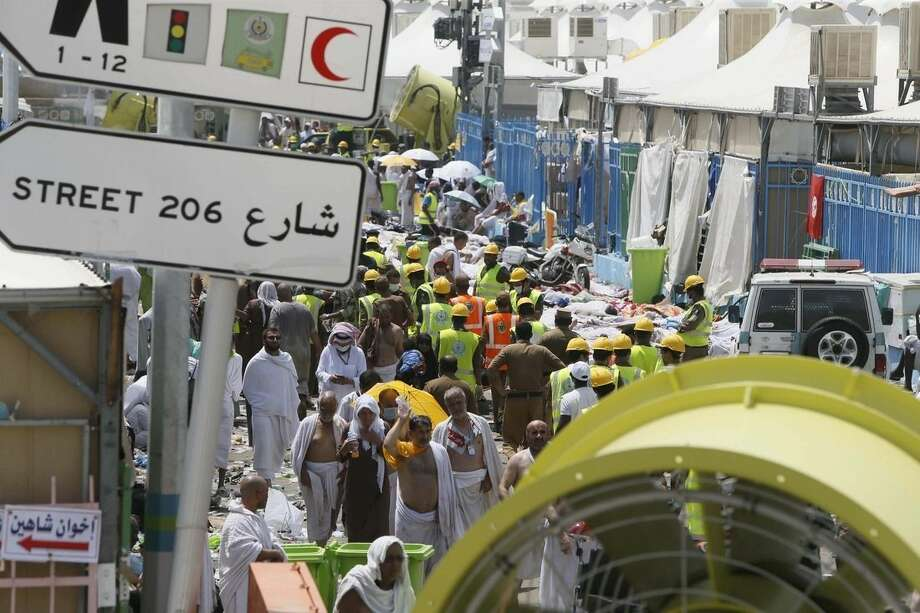 Muslim pilgrims and rescue workers gather around the victims of a stampede in Mina, Saudi Arabia during the annual hajj pilgrimage on Thursday, Sept. 24, 2015. Hundreds were killed and injured, Saudi authorities said. The crush happened in Mina, a large valley about five kilometers (three miles) from the holy city of Mecca that has been the site of hajj stampedes in years past. (AP Photo)
