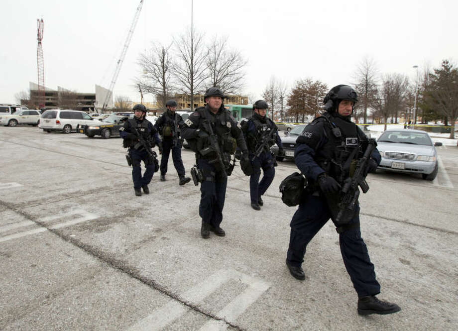 Police move in from a parking lot to the Mall in Columbia after reports of a multiple shooting, Saturday Jan. 25, 2014 Howard County, Md. Police in Maryland say three people died Saturday in a shooting at a mall in suburban Baltimore, including the presumed gunman. ( AP Photo/Jose Luis Magana)