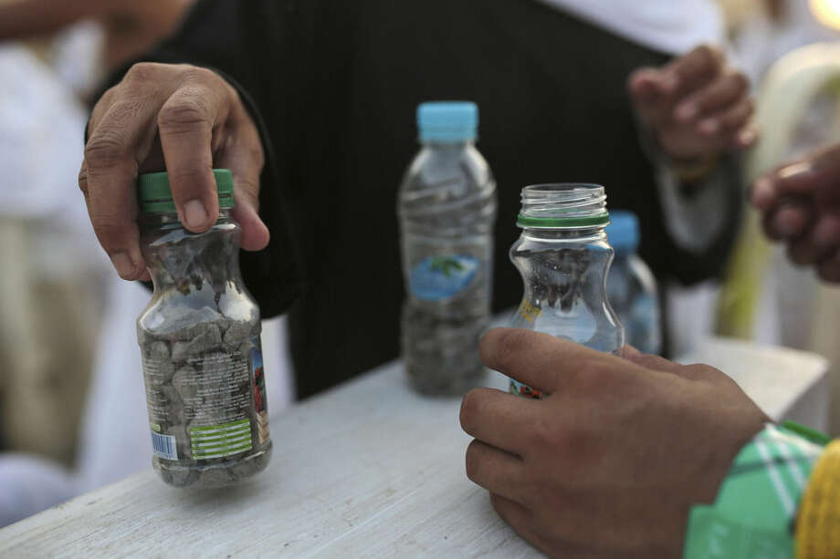 """Muslim pilgrims collect stones in bottles as they make their way to cast stones at a pillar symbolizing the stoning of Satan, in a ritual called """"Jamarat,"""" the last rite of the annual hajj, on the first day of Eid al-Adha, in Mina near the holy city of Mecca, Saudi Arabia, Thursday, Sept. 24, 2015. (AP Photo/Mosa'ab Elshamy)"""