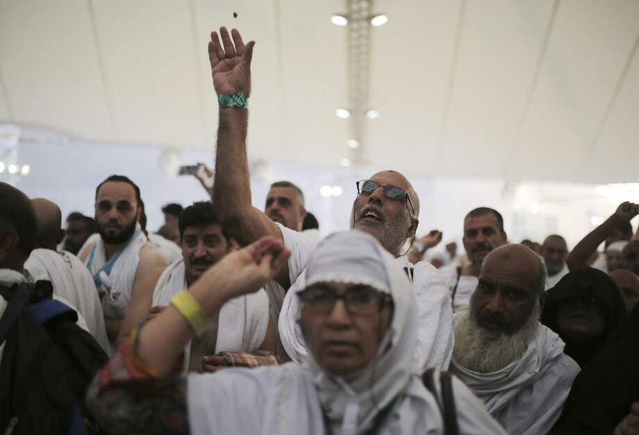 """Muslim pilgrims cast stones at a pillar symbolizing the stoning of Satan, in a ritual called """"Jamarat,"""" the last rite of the annual hajj, on the first day of Eid al-Adha, in Mina near the holy city of Mecca, Saudi Arabia, Thursday, Sept. 24, 2015. Saudi Arabia's civil defense directorate says at least 150 people have been killed in a stampede at the annual hajj pilgrimage. (AP Photo/Mosa'ab Elshamy)"""
