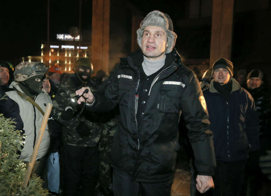 Opposition leader Vitali Klitschko gives instructions to protesters prior to seizing the Ukrainian House in central Kiev, Ukraine, early Sunday, Jan. 26, 2014. Opposition leader Arseniy Yatsenyuk told journalists early on Sunday that the Ukrainian opposition was ready to take responsibility for the country's future but only on its own terms. (AP Photo/Efrem Lukatsky)