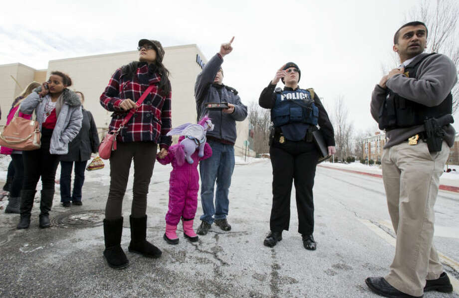 Law enforcement officers escort visitors from The Mall in Columbia, Md., Saturday, Jan. 25, 2014, to a nearby parking lot following a shooting. Police say three people died at the mall including the presumed gunman. (AP Photo/Manuel Balce Ceneta)