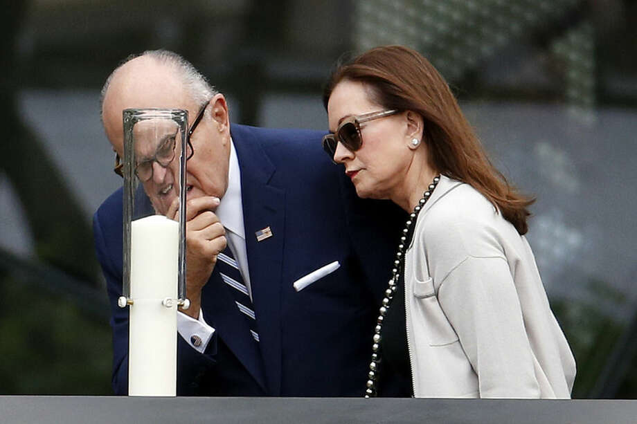 Former New York City Mayor Rudy Giuliani, left, and his wife, Judith Giuliani, look at a candle on the South Pool at the site of the World Trade Center in New York, Friday, Sept. 25, 2015. Pope Francis is expected to visit the 9/11 memorial as part of his five-day trip to the United States. (AP Photo/Julio Cortez, Pool)