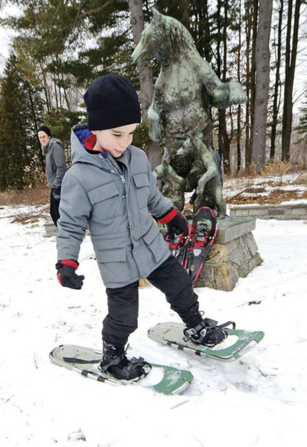 Hour photo / Erik Trautmann 6 year old Donovan Gallagher tries on a p[air of snowshoes during the Earthplace 2014 Winterfest in Westport Saturday.