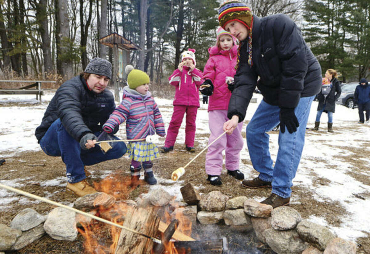 Hour photo / Erik Trautmann Lucas and Zoe Macniak and Maddie, Emily and David Beggs roast marshmallows during the Earthplace 2014 Winterfest in Westport Saturday.