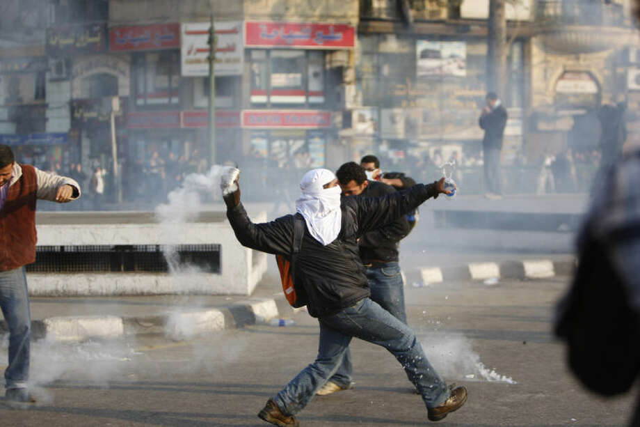 FILE - In this Jan. 25, 2011 file photo, a protester throws back a tear gas canister toward police at a demonstration in Cairo, Egypt. As Egyptians mark the third anniversary of their revolution against autocrat Hosni Mubarak in the name of democracy, there has been a powerful sign of the country's stunning reversals since: letters of despair by some of the prominent activists who helped lead the uprising, leaked from the prisons where they are now jailed. The letters show a daunted and broken spirit, no longer speaking of imminent democracy, but of injustices and a failed struggle.(AP Photo/Nasser Nasser, File)