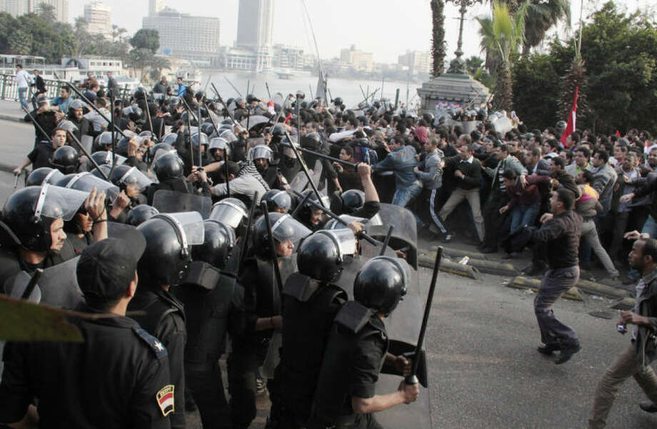 FILE - In this Jan. 25, 2011 file photo, police face demonstrators in Cairo, during a Tunisia-inspired demonstration to demand the end of President Hosni Mubarak's nearly 30 years in power. As Egyptians mark the third anniversary of their revolution against autocrat Hosni Mubarak in the name of democracy, there has been a powerful sign of the country's stunning reversals since: letters of despair by some of the prominent activists who helped lead the uprising, leaked from the prisons where they are now jailed. The letters show a daunted and broken spirit, no longer speaking of imminent democracy, but of injustices and a failed struggle.(AP Photo, File)
