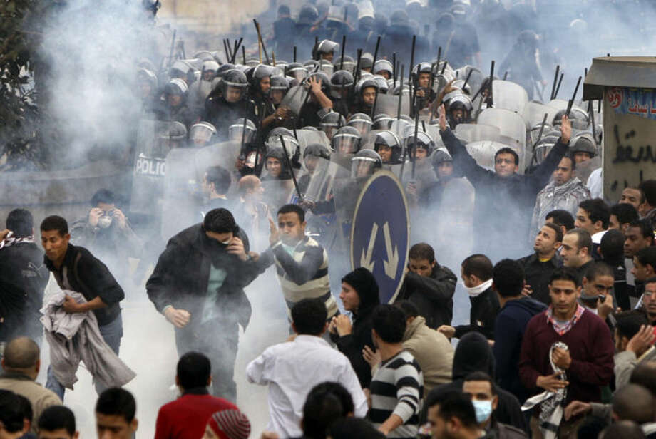 FILE - In this Friday, Jan. 28, 2011 file photo, Egyptian anti-government activists clash with riot police in Cairo, Egypt. As Egyptians mark the third anniversary of their revolution against autocrat Hosni Mubarak in the name of democracy, there has been a powerful sign of the country's stunning reversals since: letters of despair by some of the prominent activists who helped lead the uprising, leaked from the prisons where they are now jailed. The letters show a daunted and broken spirit, no longer speaking of imminent democracy, but of injustices and a failed struggle.(AP Photo/Ben Curtis, File)