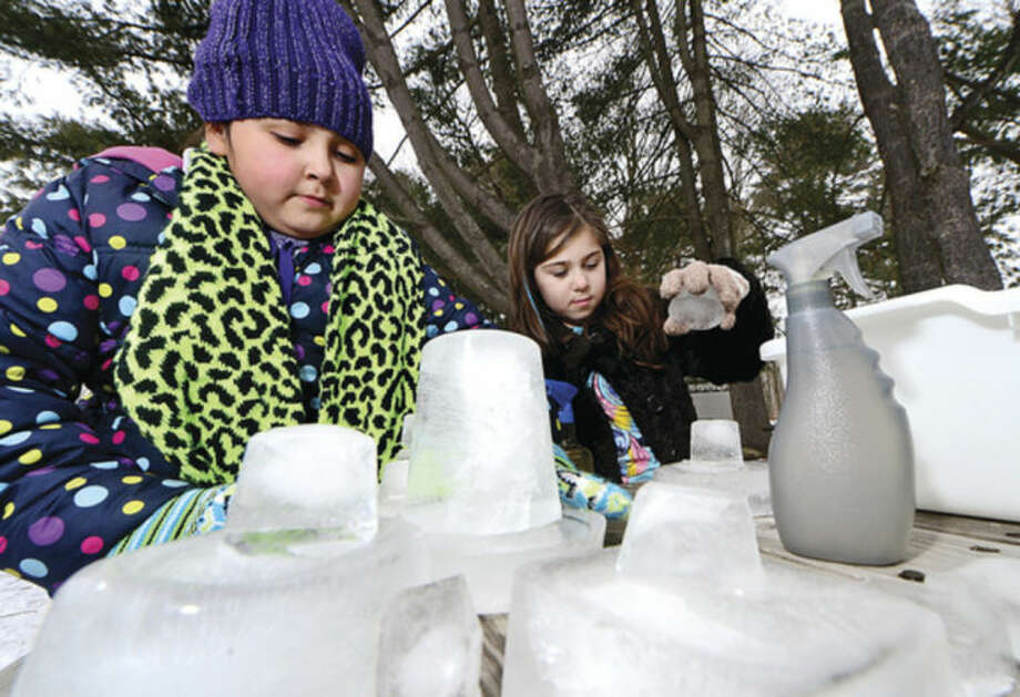 Hour photo / Erik Trautmann Allie Velasquez and Elle Delima build ice scuptures during the Earthplace 2014 Winterfest in Westport Saturday.