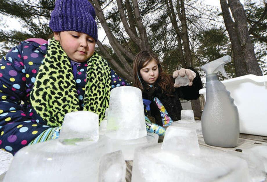 Hour photo / Erik Trautmann Allie Velasquez and Elle Delima build ice scuptures during the Earthplace 2014 Winterfest in Westport Saturday.