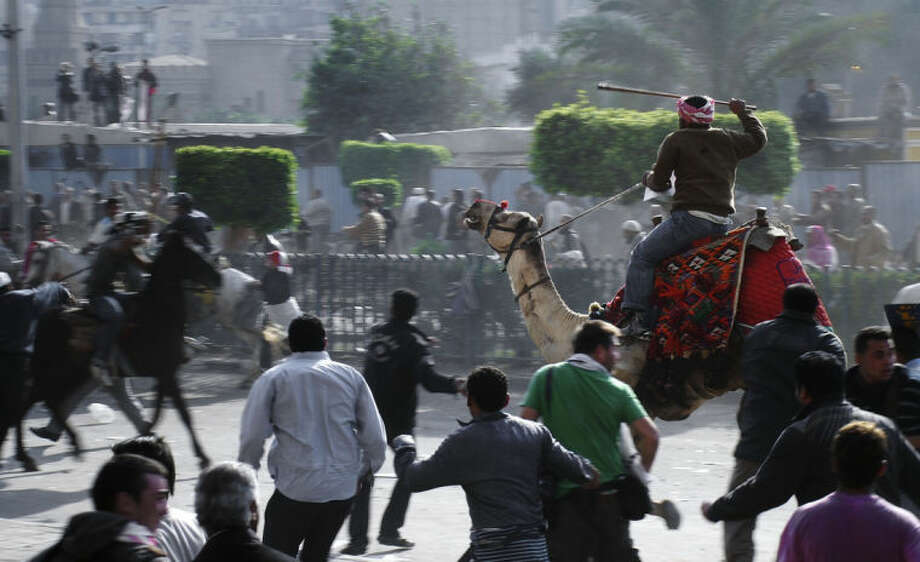 FILE - In this Wednesday, Feb. 2, 2011 file photo, supporters of President Hosni Mubarak, riding camels and horses, fight with anti-Mubarak protesters in Cairo, Egypt. As Egyptians mark the third anniversary of their revolution against autocrat Hosni Mubarak in the name of democracy, there has been a powerful sign of the country's stunning reversals since: letters of despair by some of the prominent activists who helped lead the uprising, leaked from the prisons where they are now jailed. The letters show a daunted and broken spirit, no longer speaking of imminent democracy, but of injustices and a failed struggle.(AP Photo/Mohammed Abu Zaid, File)