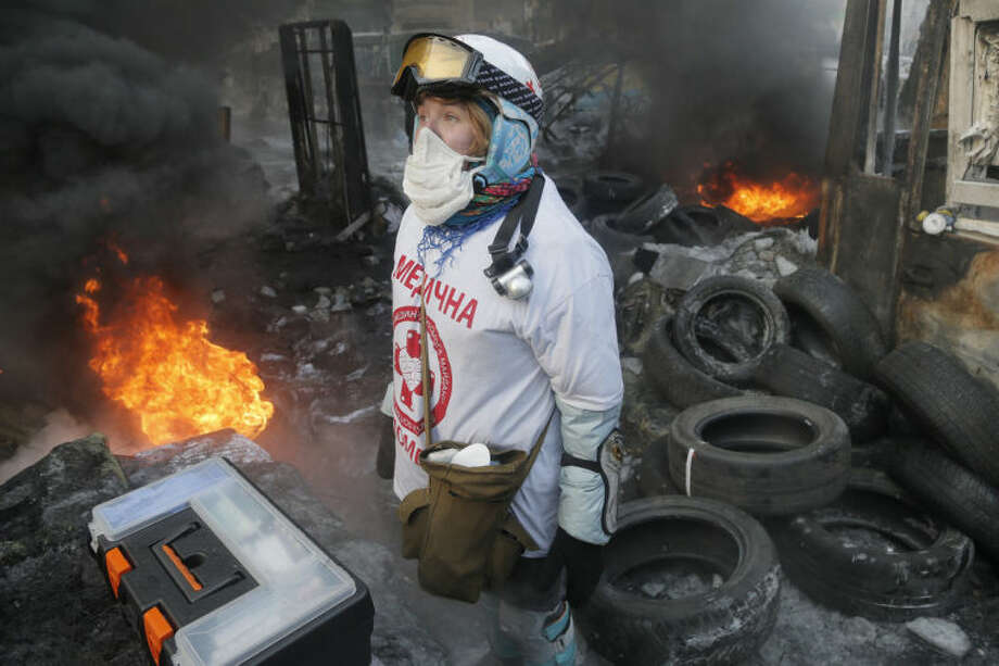 A medical volunteer looks at a clash between protesters and riot police in central Kiev, Ukraine, Saturday Jan. 25, 2014. Ukraine's Interior Ministry has accused protesters in Kiev of capturing two of its officers as violent clashes have resumed in the capital and anti-government riots spread across Ukraine. (AP Photo/Efrem Lukatsky)