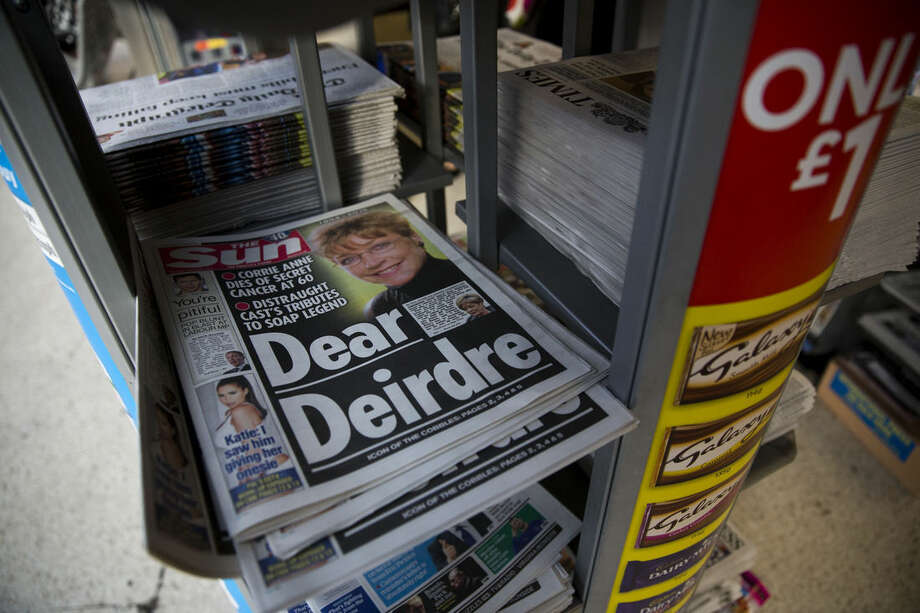 Copies of The Sun newspaper are displayed for sale in a shop in London, Tuesday, Jan. 20, 2015. Has the sun set on the topless models of Britain's tabloid press? For 45 years, the Rupert Murdoch-owned tabloid The Sun has featured topless models called Page 3 girls — photos that have long drawn protests from feminists. On Monday, it showed model Rosie Huntington-Whitely wearing a bra and the Murdoch owned Times newspaper reported Tuesday that it understands topless models will no longer appear on page 3. (AP Photo/Matt Dunham)