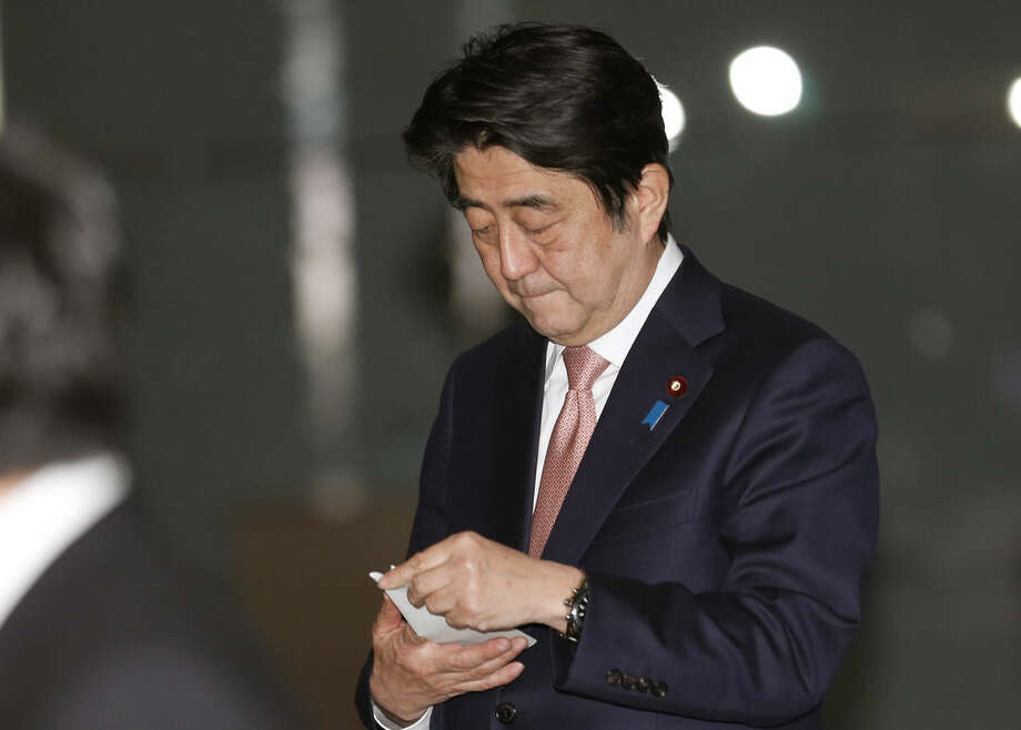 Japan's Prime Minister Shinzo Abe sees a memo before his briefing to journalists following a meeting at the prime minister's official residence in Tokyo Wednesday, Jan. 21, 2015. Japan is doing all it can as it races against time to free two hostages the Islamic State group is threatening to kill within 72 hours, Abe said, vowing never to give in to terrorism. Abe returned to Tokyo from a six-day Middle East tour slightly ahead of schedule and convened a Cabinet meeting soon after. (AP Photo/Shizuo Kambayashi)