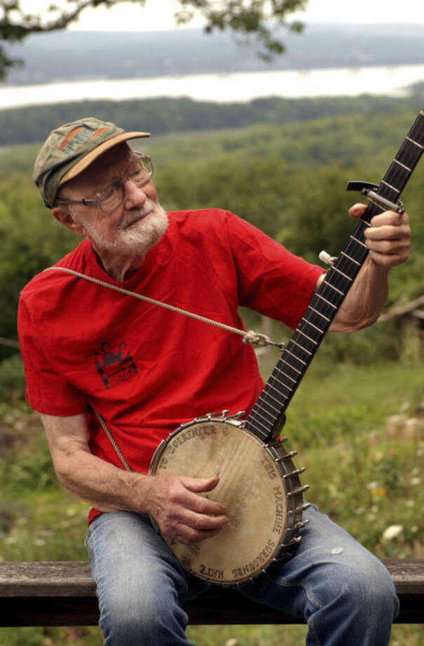 FILE - In this Tuesday, July 27, 2004 file photo, Pete Seeger, 85, sits on his porch above the Hudson River at Beacon, N.Y. and plays a Woody Guthrie song on his banjo. Seeger died on Monday Jan. 27, 2014, at the age of 94. (AP Photo/Jim McKnight)