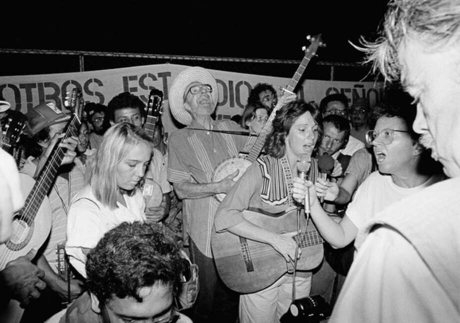FILE - In this Monday, Feb. 1, 1988 file photo, a group of Americans, including Pete Seger, center with banjo, and Nicaraguans stage a demonstration in front of the U.S. embassy in Managua, Nicaragua to protest Contra aid. Seeger died on Monday Jan. 27, 2014, at the age of 94. (AP Photo/Mauricio Orozco)