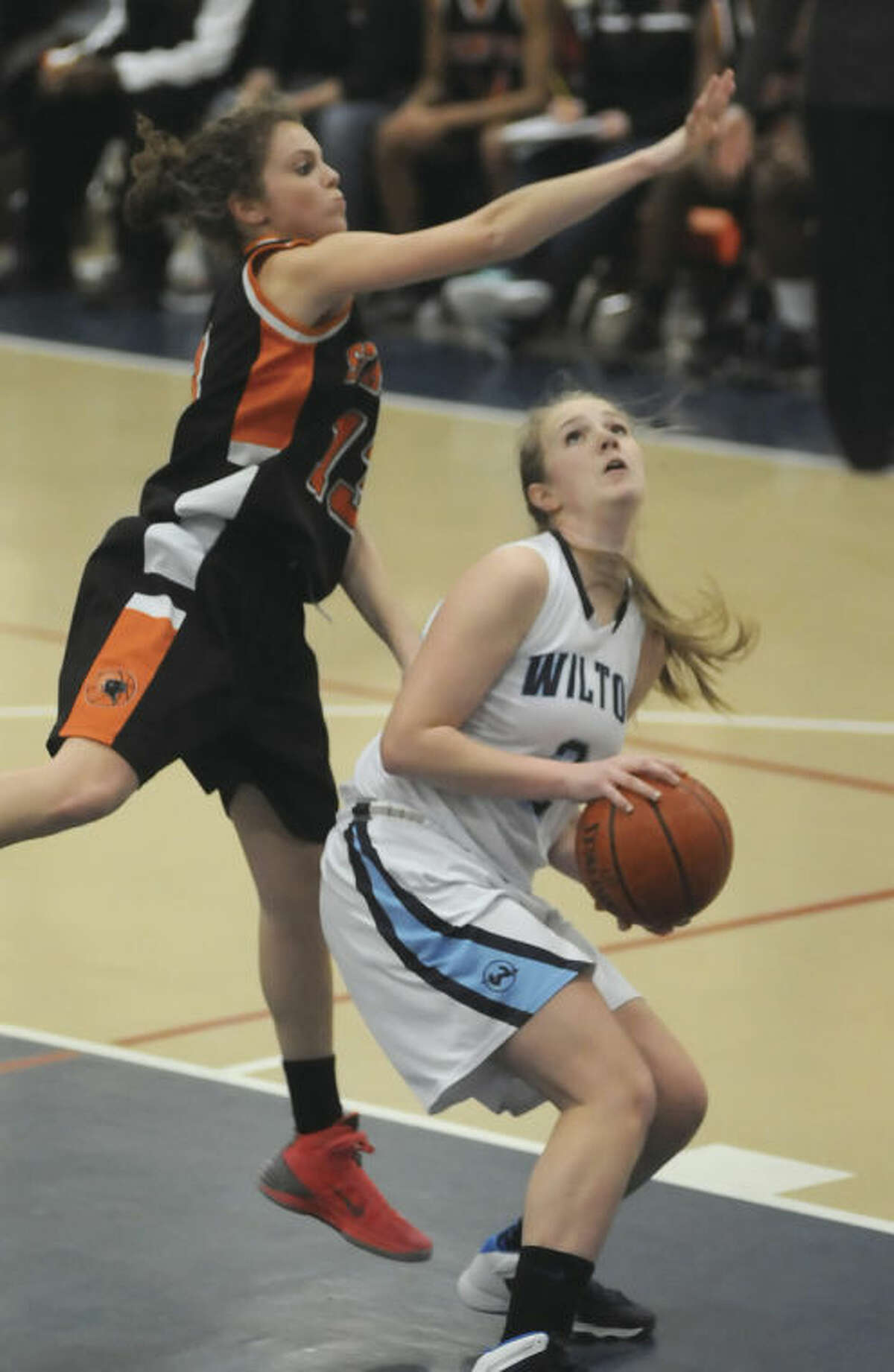Hour photo/John Nash Wilton's Erin Cunningham, right, looks toward the hoop right before getting fouled by Stamford's Maxine Fodiman during the first half of Monday's FCIAC girls basketball game at the Zeoli Field House. Stamford ended Wilton's undefeated run with a 55-50 win.