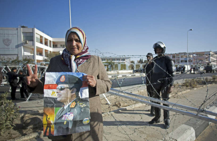 An Egyptian woman flashes the victory sign and holds a picture of Egypt's Defense Minister Field Marshal Abdel-Fattah el-Sissi, while police guard outside the courthouse during the trial of ousted Egyptian President, Mohammed Morsi, in Cairo, Egypt, Tuesday, Jan. 28, 2014. Morsi has arrived in Cairo by helicopter from Borg al-Arab prison near Alexandria for the start of his trial Tuesday over charges he and some 130 others face for prison breaks during the country's 2011 revolution, the state news agency reported. (AP Photo/Khalil Hamra)