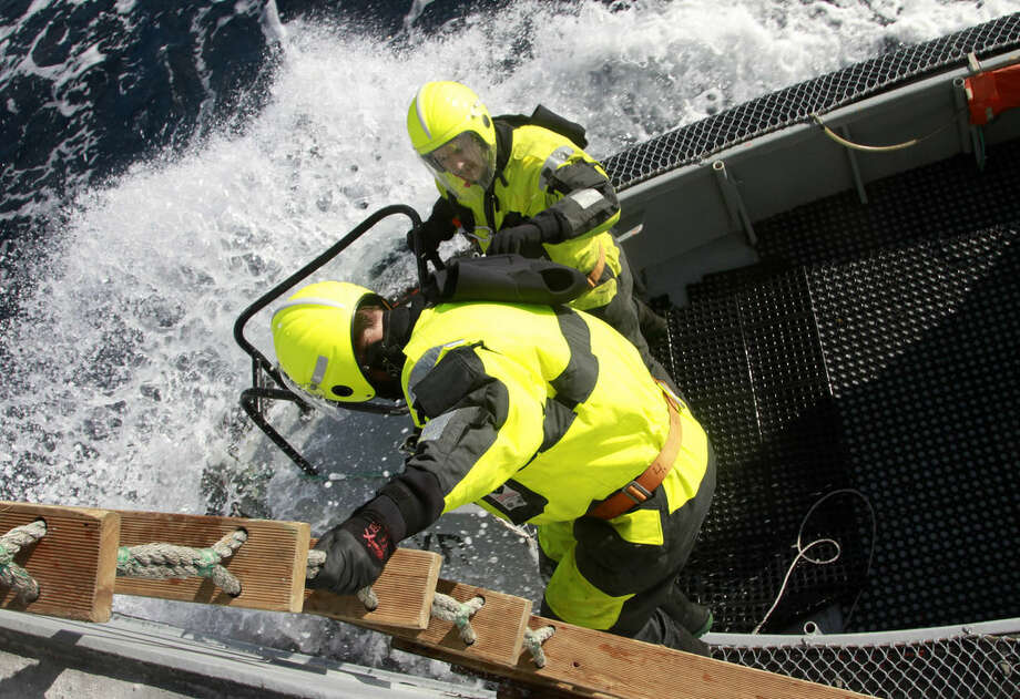 In this Jan. 14, 2015 photo, sailors from the Icelandic Coast Guard cutter Tyr practice descending from the ship during a training exercise with protective gear. The ship is part of the 19-nation Operation Triton patrolling the seas for the rising numbers of migrants, especially from Syria and Iraq, that are trying to reach Europe through its southern borders. (AP Photo/Paul Schemm)