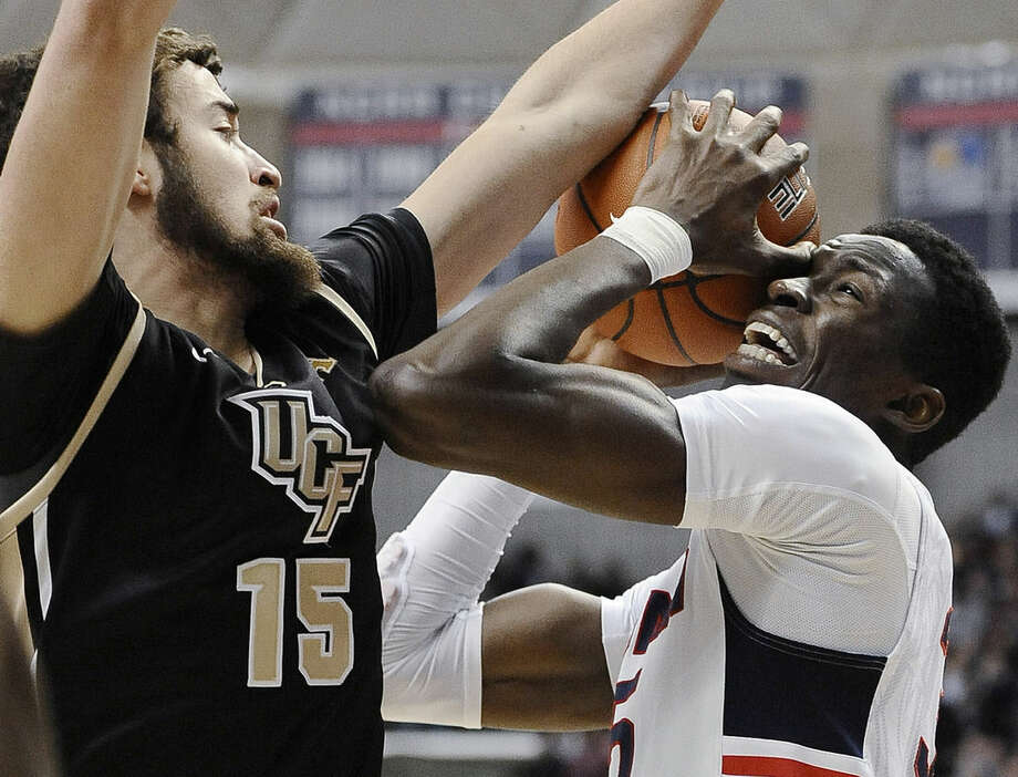 UCF's Dylan Karell, left, guards Connecticut's Amida Brimah during the first half of an NCAA college basketball game, Thursday, Jan. 22, 2015, in Storrs, Conn. (AP Photo/Jessica Hill)