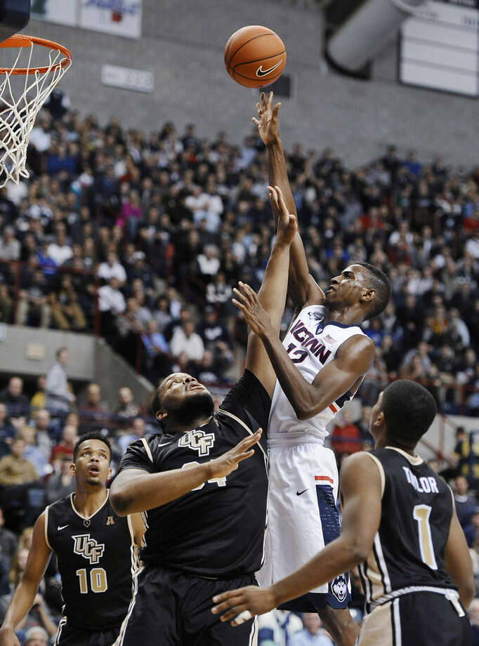 UConn's Kentan Facey, shoots as UCF's Adonys Henriquez, left, Justin McBride, center, and B.J. Taylor, right, defend during the second half of an NCAA college basketball game, Thursday, Jan. 22, 2015, in Storrs, Conn. UConn won 67-60. (AP Photo/Jessica Hill)