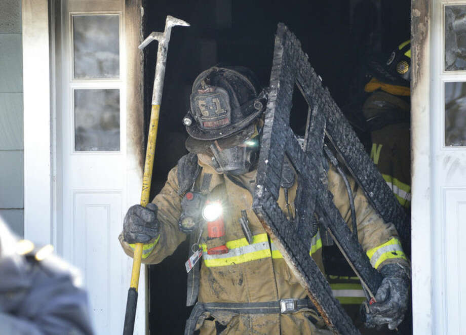 Hour Photo/Alex von Kleydorff. Wilton firefighter Kevin Locher removes some debris to clear the entrance of a house on Valeview Rd in Wilton on Tuesday. Emergency personnel responded to the house fire with mutual aid from Norwalk and were able to stop the fire quickly