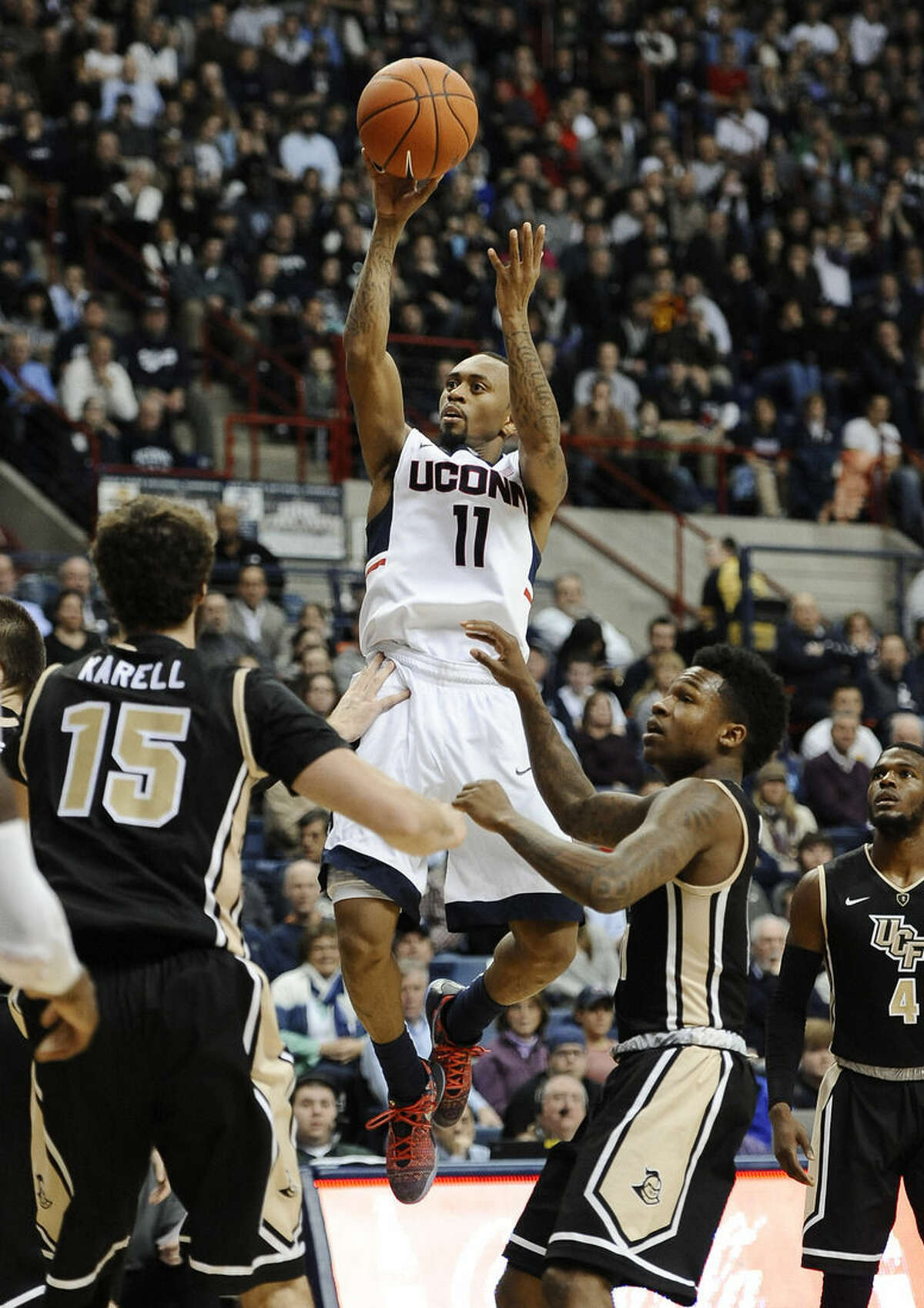 Connecticut's Ryan Boatright shoots over UCF's Dylan Karell, left, and Brandon Goodwin, right, during the second half of an NCAA college basketball game, Thursday, Jan. 22, 2015, in Storrs, Conn. Connecticut won 67-60. (AP Photo/Jessica Hill)