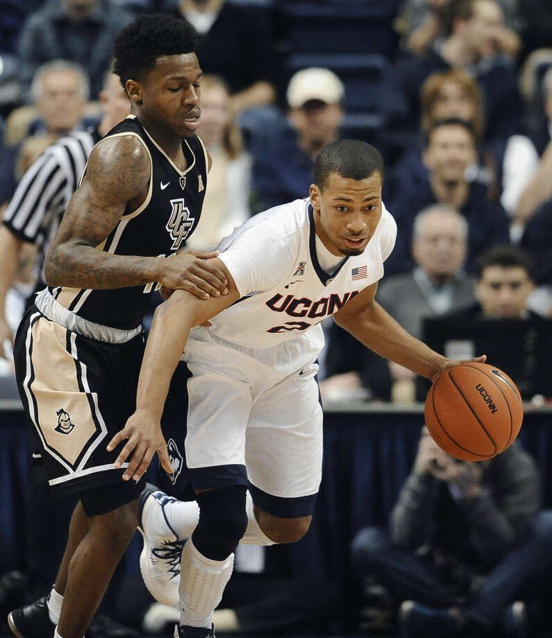 UConn's Omar Calhoun, right, dribbles past UCF's Brandon Goodwin, left, during the first half of an NCAA college basketball game, Thursday, Jan. 22, 2015, in Storrs, Conn. UConn won 67-60. (AP Photo/Jessica Hill)