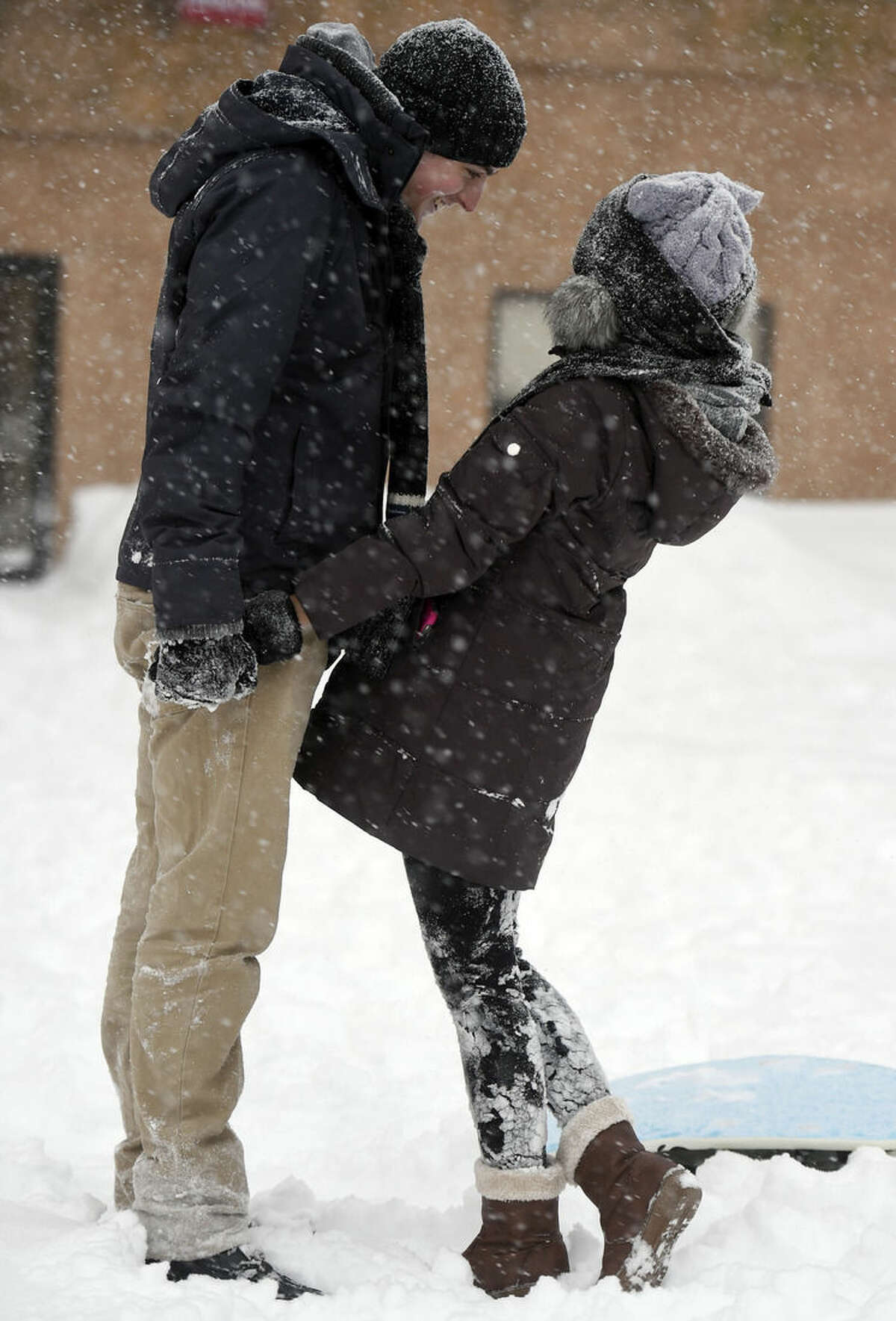 Pear Sutuntanjai, right, and Aaron Gionet frolic in the snow along Bath St. in downtown Norwich, Conn., Tuesday, Jan. 27, 2015, after a winter storm dumped nearly 2-feet of snow in the region. Sutuntanjai is from Thailand and interning at the nearby Foxwoods Resort Casino. This is her first ever experience of snow. (AP Photo/The Day, Sean D. Elliot) MANDATORY CREDIT