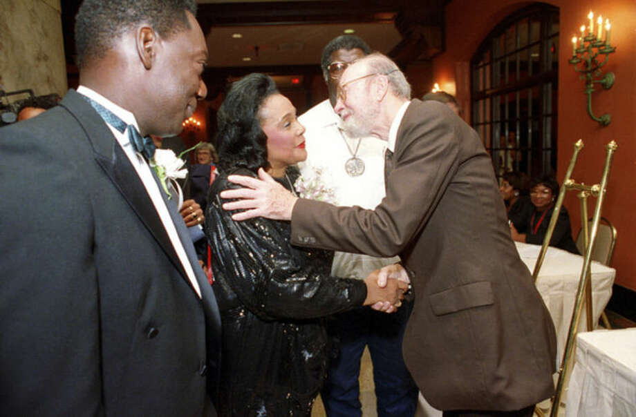 FILE - In this Tuesday night, July 2, 1991 file photo, Coretta Scott King is welcomed by folk singer Pete Seeger as she arrives at a banquet in Memphis, Tenn. during an event leading to the dedication of the National Civil Rights Museum. Seeger died on Monday Jan. 27, 2014, at the age of 94. (AP Photo/Mark Humphrey)