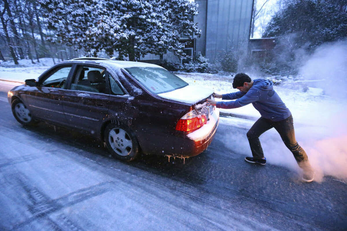 Good Samaritan Sammy Rouchdi pushes stranded motorist Cameron Scheeler up an iced over hill on Womack Road after he became stuck on the ice trying to get home on Tuesday, Jan. 28, 2014, in Dunwoody. (AP Photo/Atlanta Journal-Constitution, Curtis Compton)