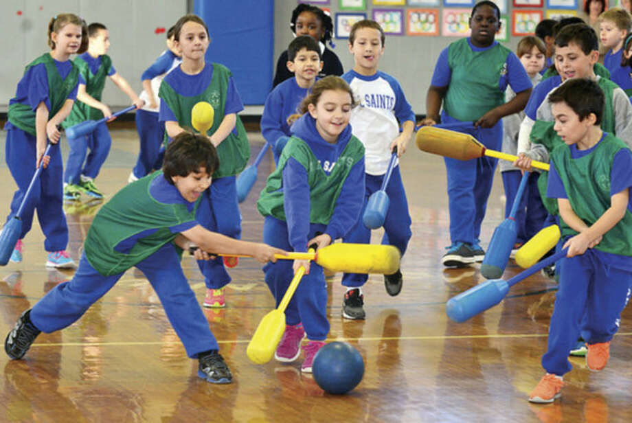 Hour photo / Erik Trautmann All Saints Catholic School 3rd grders Sebastian Guzman and Lucia Cirafalco particpate in a floor hockey contest as the school holds an Olympic games for students Wednesday during Student Appreciation Day for Catholic School Week.
