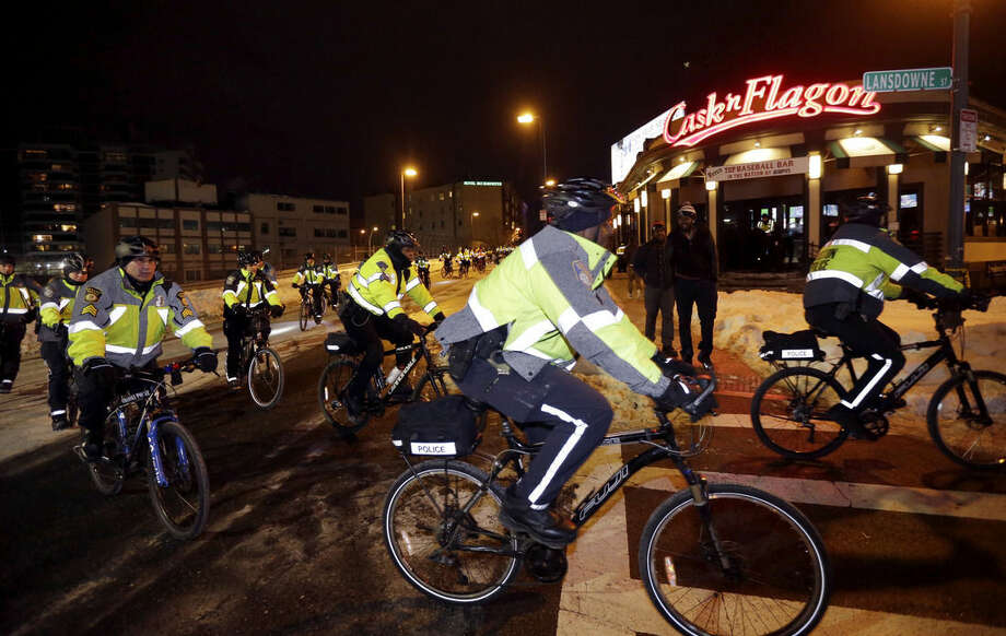 Boston Police bicycle patrolmen ride near Kenmore square after Sunday, Feb. 1, 2015, in Boston, after theNew England Patriots won the NFL Super Bowl XLIX football game against the Seattle Seahawks 28-24 in Glendale, Ariz.(AP Photo/Steven Senne)