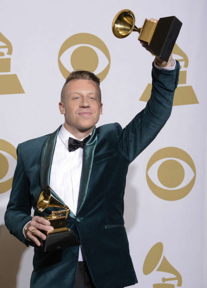 "Macklemore poses in the press room with two of his awards after winning for best rap performance and best rap song, for ""Thrift Shop,"" best rap album for ""The Heist"" and best new artist at the 56th annual Grammy Awards at Staples Center on Sunday, Jan. 26, 2014, in Los Angeles. (Photo by Dan Steinberg/Invision/AP)"