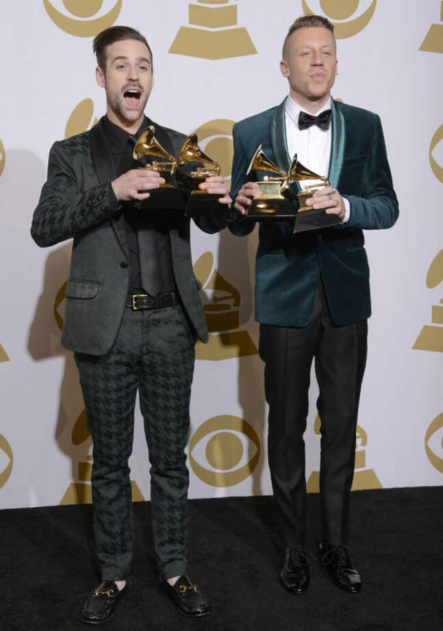 """Ryan Lewis, left, and Macklemore pose in the press room with their awards for best rap performance and best rap song, for """"Thrift Shop,"""" best rap album for """"The Heist"""" and best new artist at the 56th annual Grammy Awards at Staples Center on Sunday, Jan. 26, 2014, in Los Angeles. (Photo by Dan Steinberg/Invision/AP)"""