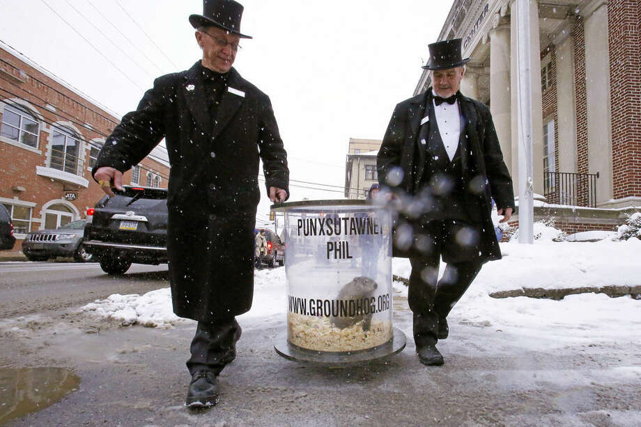 Groundhog Club co-handlers John Griffiths, right, and Ron Ploucha carry Punxsutawney Phil, the weather prognosticating groundhog, on his rounds through downtown Punxsutawney, Pa., Sunday, Feb. 1, 2015, the eve of the 129th Groundhog Day celebration on Gobbler's Knob. (AP Photo/Gene J. Puskar)