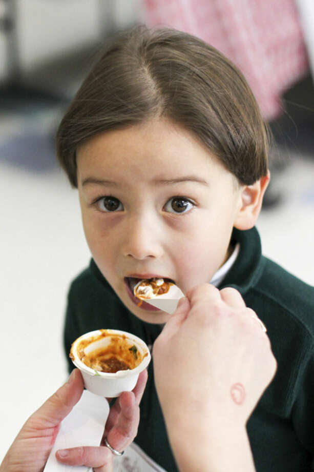 Hour photo/Chris Palermo Justin Kendrock, 4, of Westport enjoys a spoonful of chili at Chilifest at Bedford Middle School Sunday.