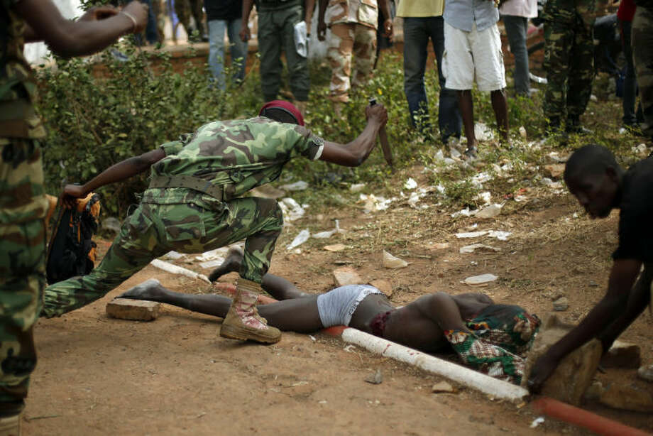 GRAPHIC CONTENT - A newly enlisted FACA (Central African Armed Forces) soldier stabs the lifeless body of a suspected Muslim Seleka militiaman moments after Central African Republic Interim President Catherine Samba-Panza addressed the troops in Bangui, Wednesday Feb. 5, 2014. The victim was lynched by hundreds of recruits. (AP Photo/Jerome Delay)