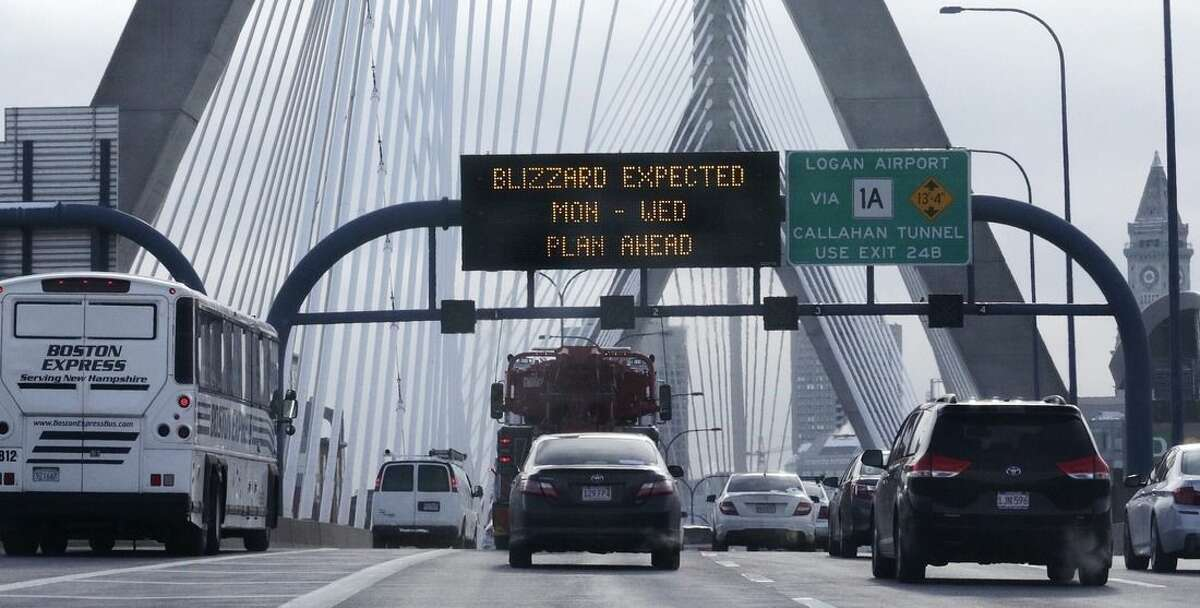 With a road sign warning of an expected blizzard, morning commuters travel across the Zakim Bunker Hill Bridge into downtown Boston., Monday, Jan. 26, 2015. The Boston area is expected to get hit with about two feet of snow in the winter storm. (AP Photo/Charles Krupa)