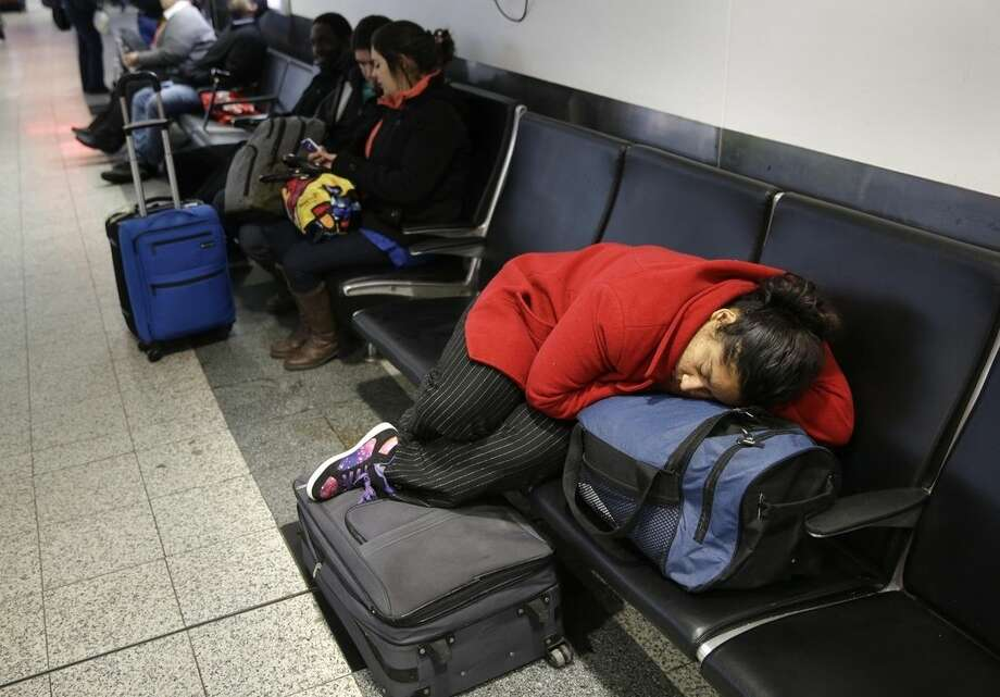 A woman sleeps on top of her luggage at LaGuardia Airport in New York, Monday, Jan. 26, 2015. Airlines canceled thousands of flights into and out of East Coast airports as a major snowstorm packing up to three feet of snow barrels down on the region. (AP Photo/Seth Wenig)