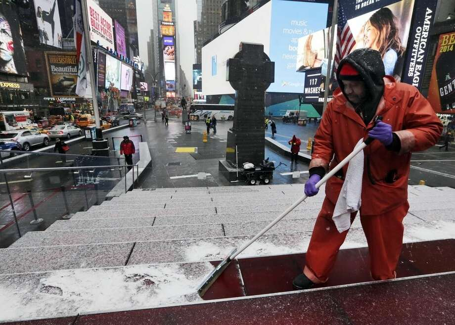 "Francisco Mathurine, of the Times Square Alliance, clears snow from the steps in Father Duffy Square in New York, Monday, Jan. 26, 2015. Officials cautioned Northeast residents to not be misled by a relatively smooth Monday morning commute, and pressed their cautions to prepare for a ""crippling and potentially historic"" storm that could bury communities from northern New Jersey to southern Maine in up to 2 feet of snow starting later in the day. (AP Photo/Richard Drew)"