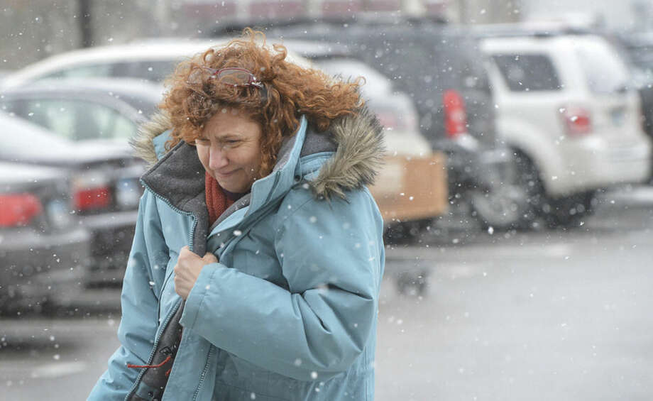 Hour Photo/Alex von KleydorffMelissa Dunsmore braces against the snow and wind as she runs some last minute errands in Norwalk Monday afternoon