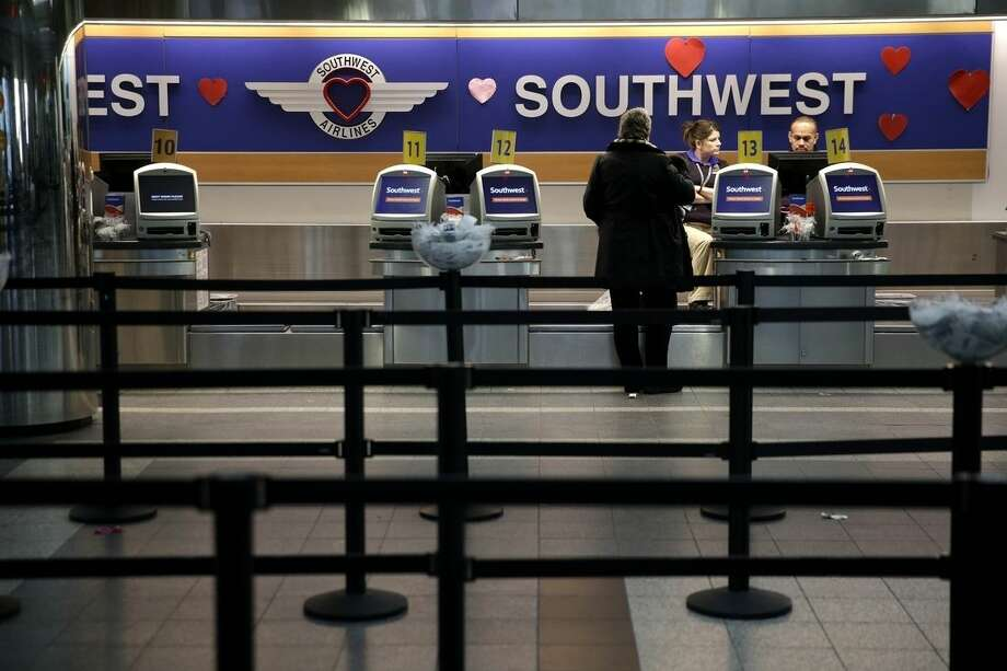 Kiosks stand empty at the Southwest Airlines counter at LaGuardia Airport on Monday morning, Jan. 26, 2015, in New York. Airlines are canceling thousands of flights into and out of East Coast airports as a major snowstorm packing up to three feet of snow barrels down on the region. (AP Photo/Seth Wenig)