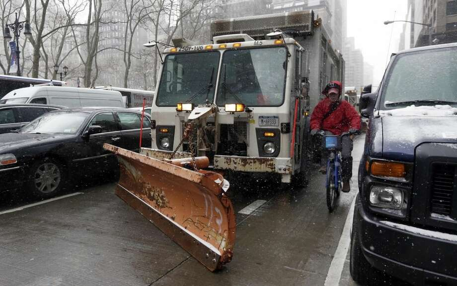 "A cyclist navigates between a New York Dept. of Sanitation truck with a snow plow attached, and park cars on New York's Sixth Ave., Monday, Jan. 26, 2015. Officials cautioned Northeast residents to not be misled by a relatively smooth Monday morning commute, and pressed their cautions to prepare for a ""crippling and potentially historic"" storm that could bury communities from northern New Jersey to southern Maine in up to 2 feet of snow starting later in the day. (AP Photo/Richard Drew)"